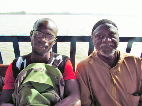 My brother, Ebrima, on his first ferry ride to the other side of the river, and my dad.