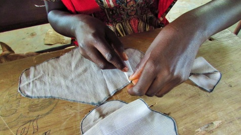 Fatou, who does tailoring work after school, makes her own menstrual pad with ease.